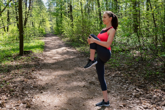 Corredor de mulher fazendo exercício de aquecimento antes de correr na floresta