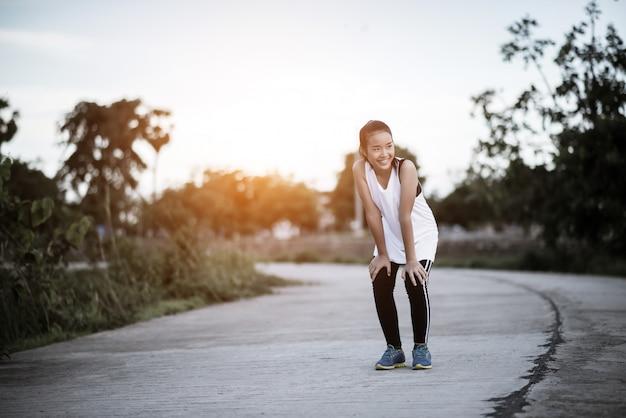 Corredor de mulher fitness cansada descansando após execução rápida