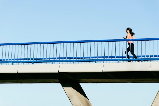 Corredor de mulher jovem aptidão correndo na ponte da cidade. conceito de esporte.