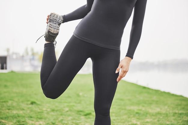 Corredor de mulher jovem fitness esticando as pernas antes de correr no parque
