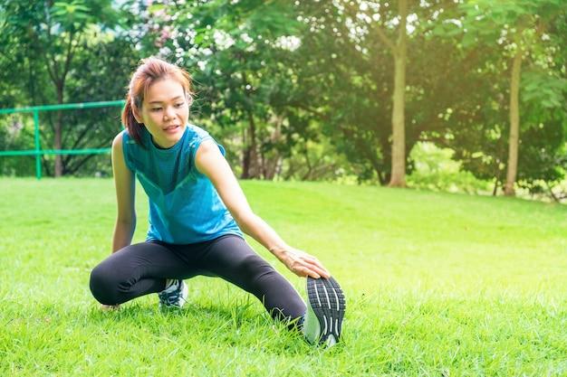 Corredor de mulher saudável jovem ásia aquecendo antes de correr no parque ao ar livre