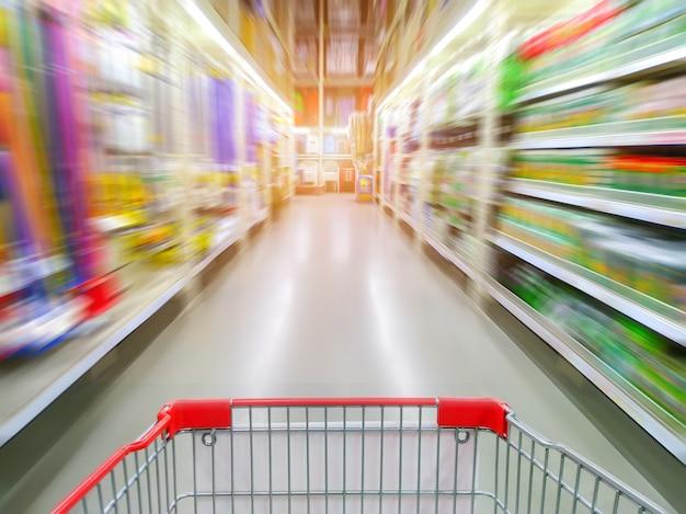 Corredor de supermercado com carrinho de compras vermelho vazio
