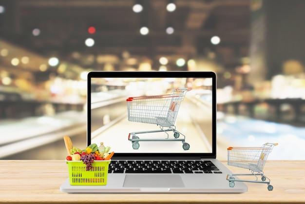 Corredor de supermercado desfocado fundo com computador laptop e carrinho de compras no conceito online de mercearia de mesa de madeira