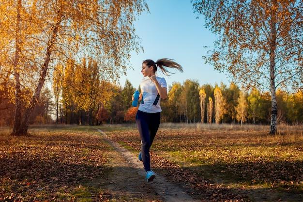 Corredor de treinamento no parque outono, mulher correndo com garrafa de água ao pôr do sol, estilo de vida ativo