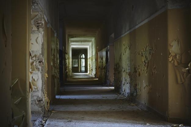 Corredor de um prédio abandonado com paredes envelhecidas sob as luzes