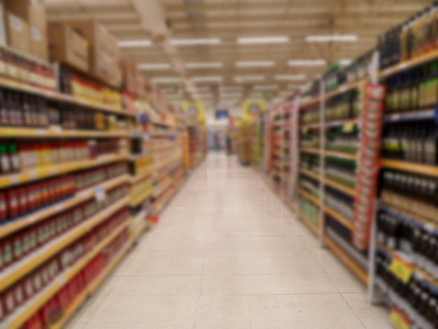 Corredor desfocado do supermercado com perspectiva das prateleiras do corredor abstrato do supermercado