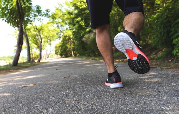 Corredor desportivo homem correndo nas estradas no parque