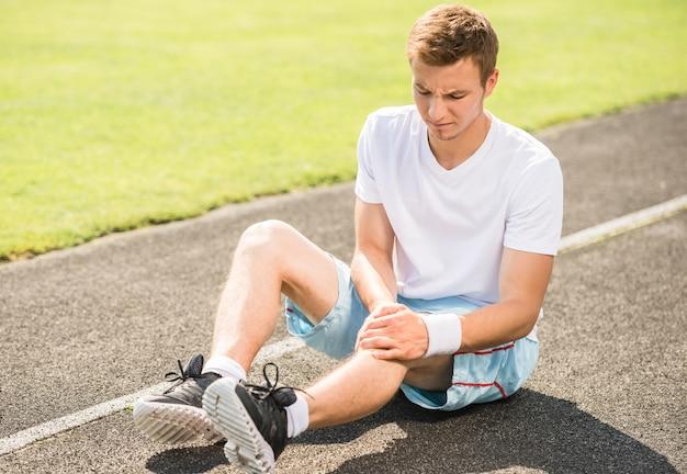 Corredor do atleta que toca no pé na dor devido ao tornozelo torcido.