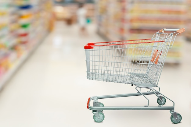 Corredor do supermercado com carrinho de compras vazio no conceito de negócio de varejo de supermercado