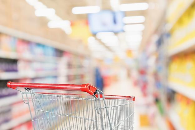 Corredor do supermercado desfocado com carrinho de compras vermelho vazio