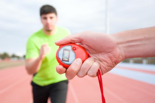 Corredor e cronômetro na pista de corrida