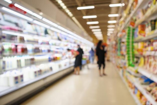 Corredor e prateleiras do supermercado com produtos lácteos na geladeira desfocar o fundo