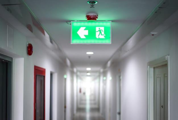 Corredor em apartamento com quartos de porta com sinal de luz verde de saída de incêndio