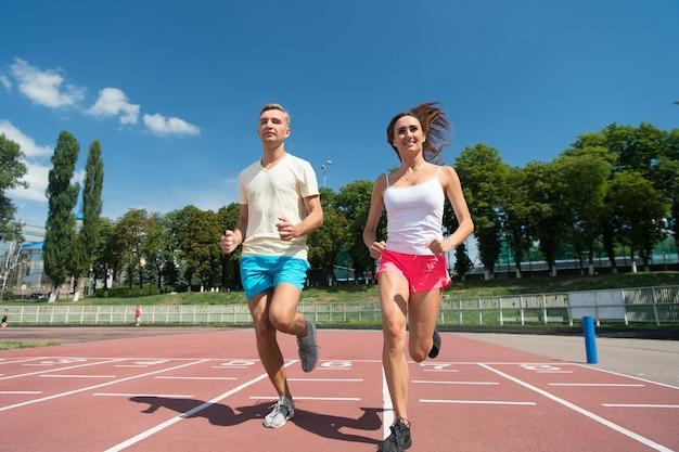 Corredor em competição e sucesso futuro. homem e mulher ensolarados ao ar livre no céu azul. casal correndo na pista da arena. esporte e boa forma saudável. treinador e treinador no treino.