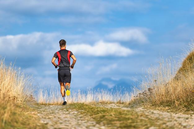 Corredor em trens de estrada de montanha para uma maratona de alta altitude