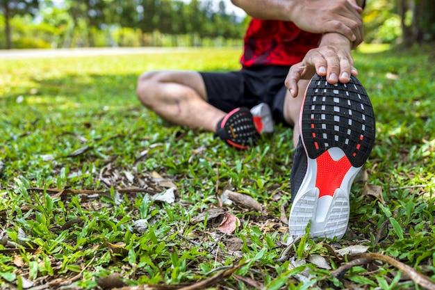 Corredor esportista aquecer seu corpo antes de começar a correr na estrada no parque