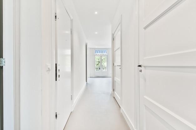 Corredor estreito com portas que conduzem a uma sala vazia e iluminada com janela em apartamento moderno
