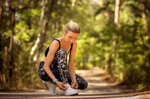 Corredor feminino amarrando o tênis em uma trilha na floresta.