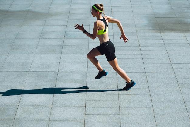 Corredor feminino, atleta de treinamento ao ar livre em dia de sol de verão.