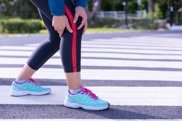Corredor feminino atleta lesão no joelho e dor.