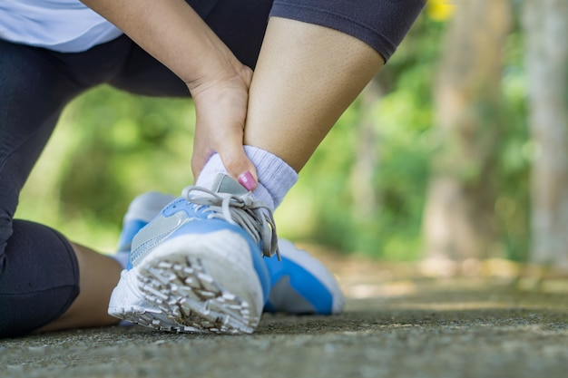 Corredor feminino caindo, acidente de ferimento do esporte