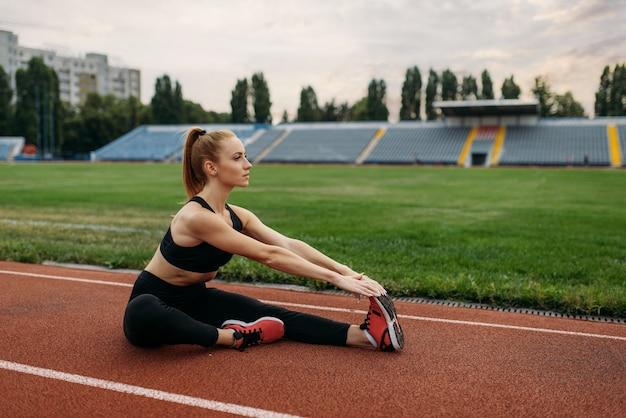 Corredor feminino em roupas esportivas, treinando no estádio. mulher fazendo exercícios de alongamento antes de correr na arena ao ar livre