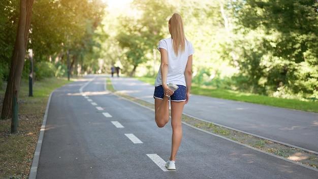 Corredor feminino esticando as pernas antes de se exercitar pela manhã no parque de verão