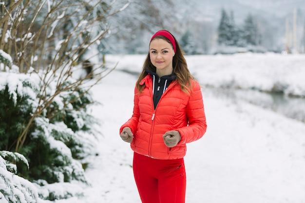 Corredor feminino, movimentando-se na neve