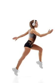 Corredor feminino profissional caucasiano, treinamento de atleta isolado no fundo branco do estúdio.