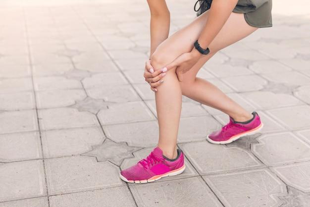 Corredor feminino, tendo, joelho, ferimento, ficar, ligado, pavimento