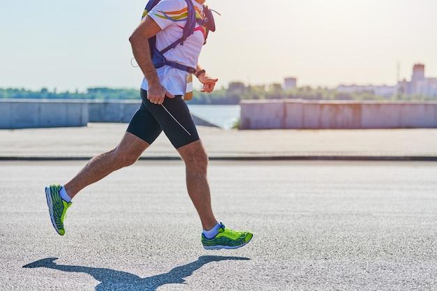 Corredor. homem atlético correndo com roupas esportivas na estrada da cidade