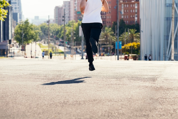 Corredor irreconhecível correndo no asfalto