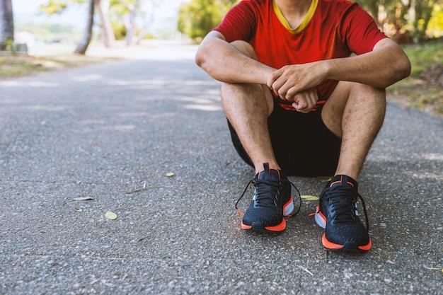 Corredor jovem descansando após a sessão de treino nas estradas no parque