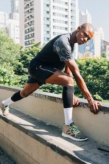 Corredor masculino africano, esticando os músculos na parte superior do telhado