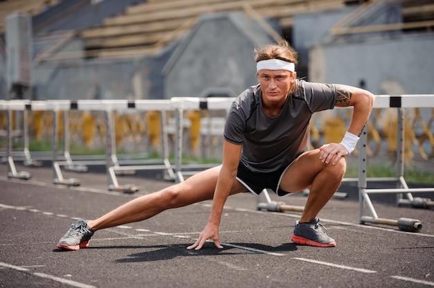 Corredor masculino, estendendo-se antes do treino.