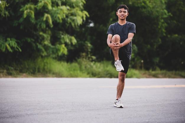 Corredor masculino fazendo exercícios de alongamento, preparando-se para treino