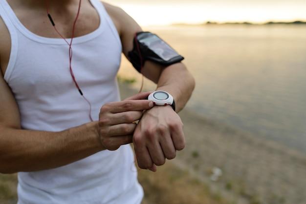 Corredor no parque usando relógio inteligente