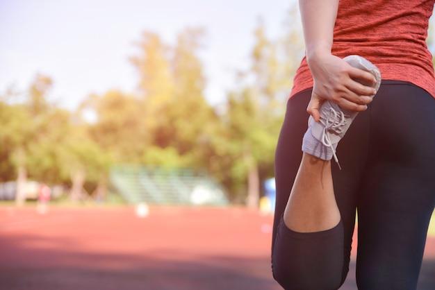 Corredor novo da mulher da aptidão que estica os pés na trilha do estádio antes de correr.