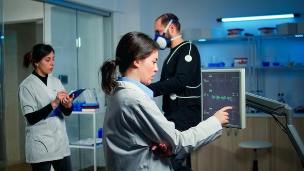 Corredor profissional do sexo masculino testando sua resistência muscular em laboratório de esportes científicos, correndo com eletrodos acoplados ao corpo, monitorando as condições de saúde, frequência cardíaca e resistência psicológica