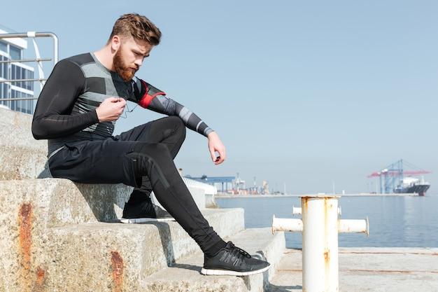 Corredor sério sentado na escada perto do mar.