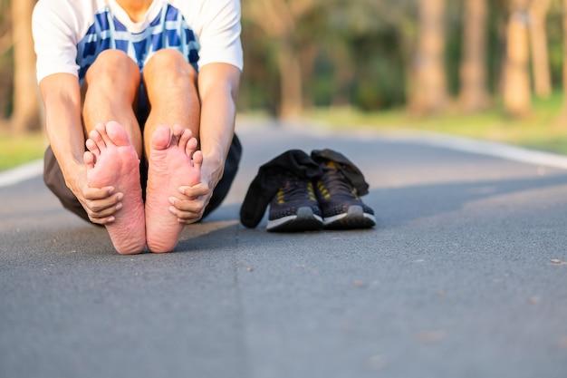 Corredor tendo pés único dor e problema após a corrida e exercício fora da manhã