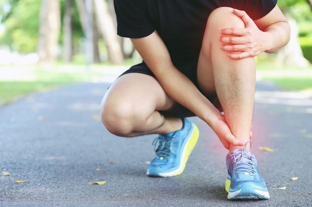 Corredor tocando o tornozelo torcido ou quebrado dolorosamente. acidente de treinamento de corredor de atleta.