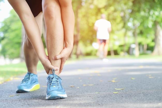 Corredor tocando o tornozelo torcido ou quebrado dolorosamente. acidente de treinamento do atleta.