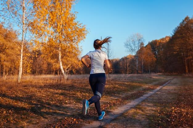 Corredor, treinamento e exercício no parque outono, mulher correndo ao pôr do sol, estilo de vida saudável e ativo