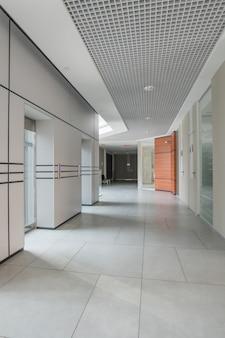 Corredor vazio do centro de negócios com ladrilhos e linhas paralelas na parede, mistura de designs minimalistas