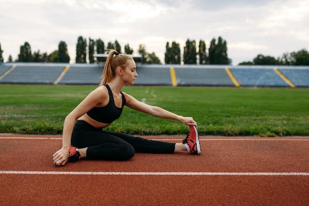 Corredora feminina em roupas esportivas, treinando no estádio