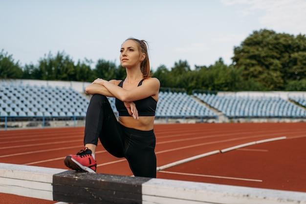 Corredora feminina, treino de alongamento no estádio