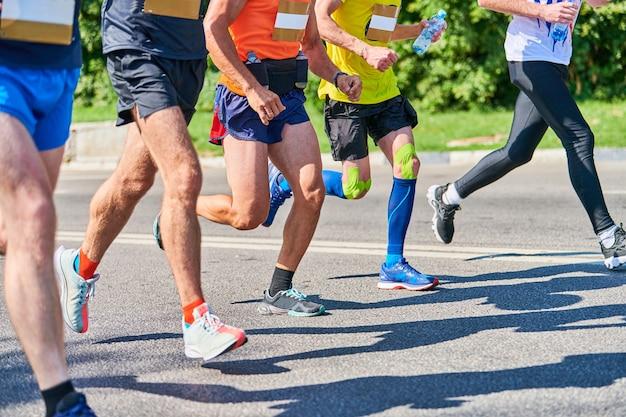 Corredores de maratona em evento esportivo de fitness nas estradas da cidade