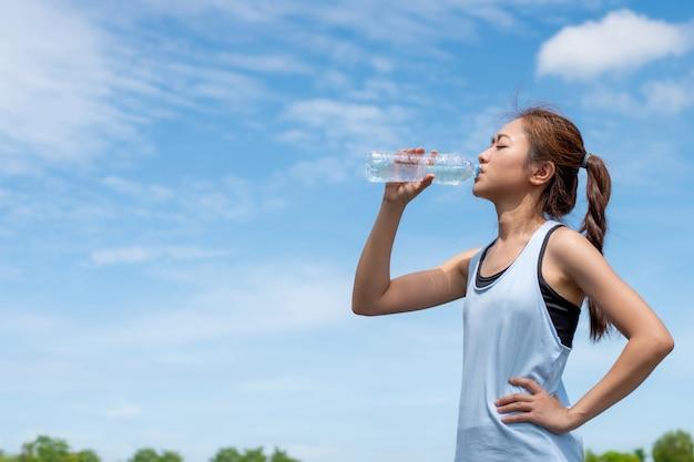 Corredores de mulher asiática estão bebendo água. após o treinamento.