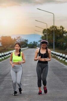 Corredores de mulheres felizes e bonitas correndo na estrada.
